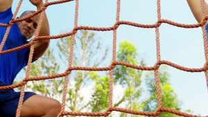 Fit man climbing a net during obstacle course 4k