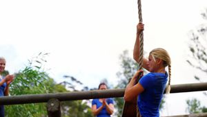 Fit woman climbing down the rope during obstacle course 4k