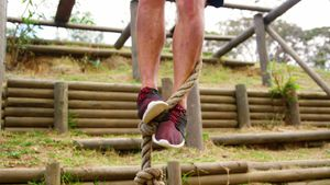 Low section of man climbing a rope during obstacle course 4k