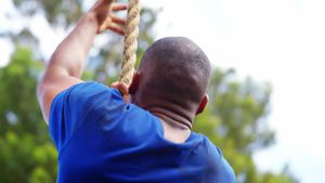Fit man climbing up the rope during obstacle course 4k