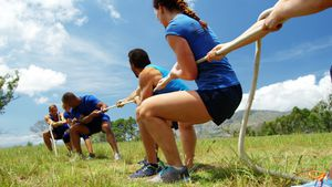 Fit people playing tug of war during obstacle training course 4k