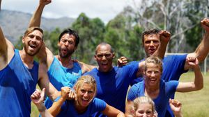 Group of fit people cheering together in boot camp 4k