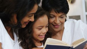 Multi-generation family reading a book in bedroom 4k