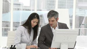 Two businesspeople working seriously at a computer
