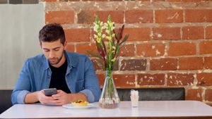 Handsome man using mobile phone at table 4k