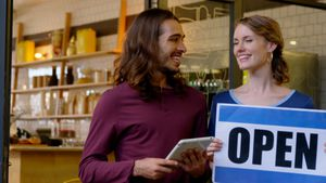 Waiter and waitress with open sign board standing at the entrance 4k