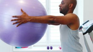 Man exercising with exercise ball 4k