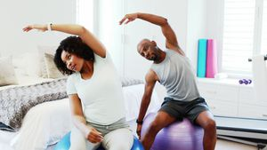 Couple exercising together on exercise ball 4k