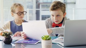 Kids as business executives discussing over laptop 4k