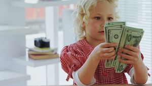 Kid as business executive counting currency note 4k