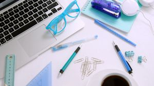 Laptop, spectacles, pen, coffee, paper clip, scale, set square and headphones on white background 4k
