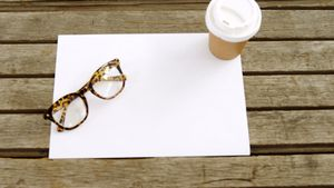 Blank paper with coffee and spectacles on wooden table 4k