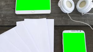 Blank papers, mobile phone, headphone and digital tablet on table 4k