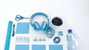 Office supplies, water bottle and blue berries on white background 4k