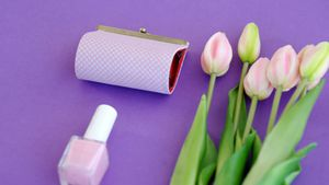 Fresh flower, purse, nail paint and mobile phone on purple background 4k