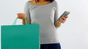 Woman standing with shopping bag and mobile phone 4k