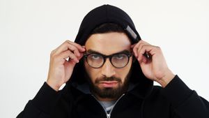 Man in hoodie wearing spectacles against white background 4k
