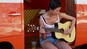 Woman playing guitar in camper van 4k