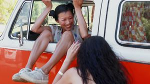 Woman sitting in camper van and posing for photo 4k