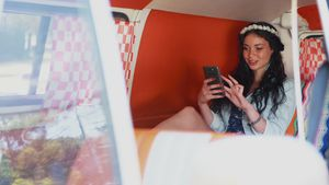 Woman using mobile phone in camper van 4k