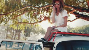 Woman relaxing in car roof on a sunny day 4k