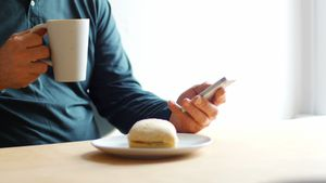 Man using mobile phone while having cup of coffee at home 4k