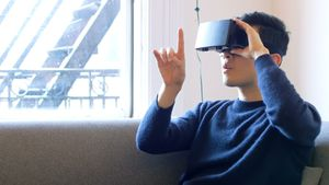 Man gesturing while using virtual reality headset in living room 4k