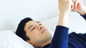 Man using mobile phone while relaxing on bed 4k