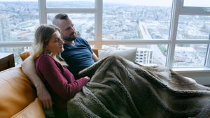 Couple watching television together in living room 4k