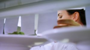 Female chef looking at an order list in the commercial kitchen 4k