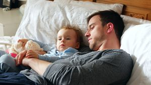 Father and baby boy relaxing in bedroom 4k