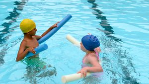 Kids swimming with noodle floater