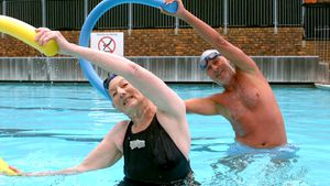 Senior couple exercising with pool noodle in swimming pool