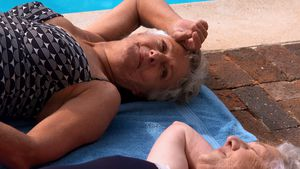 Two senior women relaxing at poolside