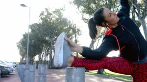 Fit woman doing stretching exercise on bollard 4k