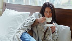 Young woman wrapped in blanket having tea 4k