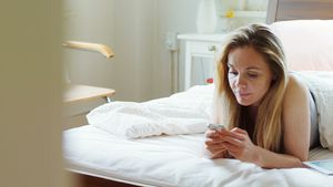Woman using mobile phone on bed 4k