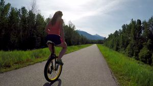 Woman riding unicycle on the road 4k