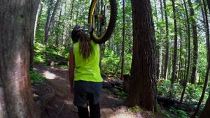 Woman carrying unicycle and passing through the forest 4k