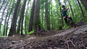 Woman riding unicycle in the forest 4k