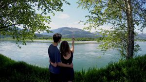 Couple standing with arm around watching the lake 4k
