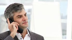 Enthusiastic businessman talking on phone