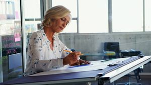 Female architect working on blueprint over drafting table 4k