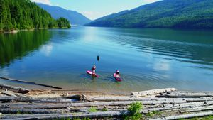 Aerial of couple on stand up paddle board oaring in river 4k