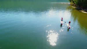 Couple on stand up paddle board oaring in river 4k