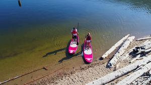 Couple parking paddleboard at riverbank on a sunny day 4k