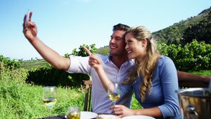 Happy couple taking selfie with mobile phone while having wine 4k
