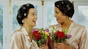 Excited bridesmaids in nightdress and hair rollers smelling the flowers 4K 4k