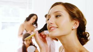 Bride getting ready for wedding and bridesmaids in background 4K 4k