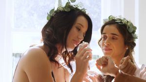 Happy bridesmaids in nightdress and head wreath are smelling and applying perfume 4K 4k